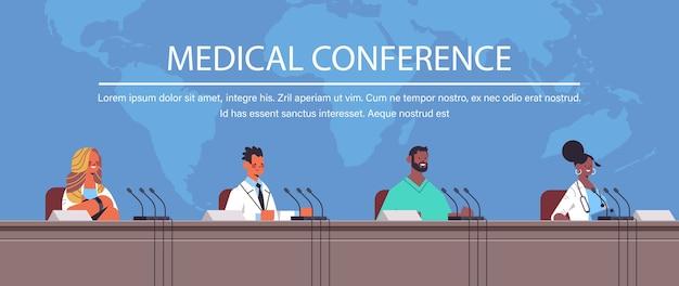 의료 회의 의학 의료 개념 세계지도 배경 복사 공간 가로 세로 벡터 일러스트 레이 션에 마이크와 트리뷴에서 연설을하는 혼합 인종 의사의 팀