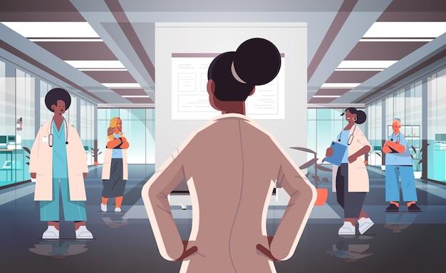Команда врачей смешанной расы в униформе обсуждает во время встречи в коридоре больницы концепция здравоохранения горизонтальная полная длина векторная иллюстрация