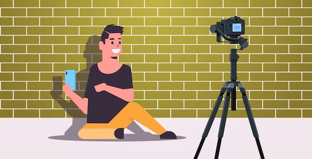 Технология блоггер тестирование смартфон человек объясняя цифровой гаджет функциональная запись видео блог с камерой на штативе потоковое вещание социальные медиа блогинг концепция полная длина горизонтальный