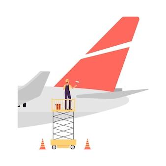 航空機の整備と修理の技術。男性整備員が飛行機の後ろを赤いペンキで塗ります。