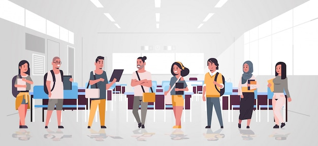 Teenage students group with backpacks holding books standing together education concept modern university classroom interior  horizontal full length