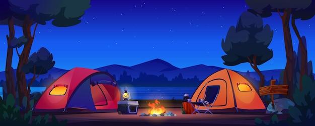 호수 밤 숲에 텐트와 불타는 모닥불
