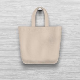 Текстурированная biege сумка вися на деревянной текстурированной стене. реалистично для шоппинга.
