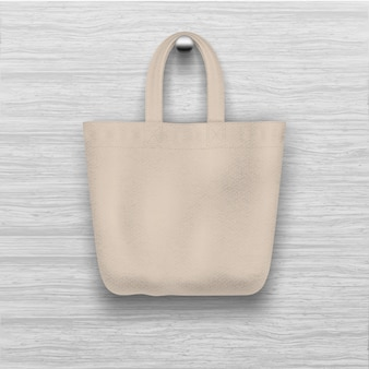 Textile  textured biege tote bag hanging on the wooden  textured wall. realistic    for  shopping .