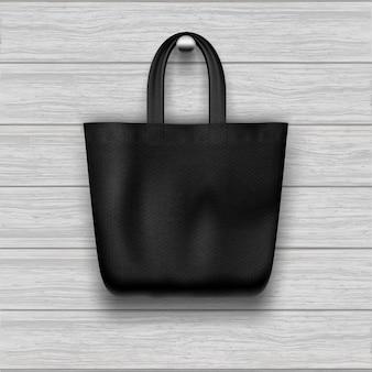 Текстурированная черная сумка висит на деревянной планке текстурированные стены.