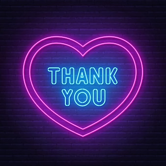 Thank you neon sign in a heart-shaped frame on brick wall