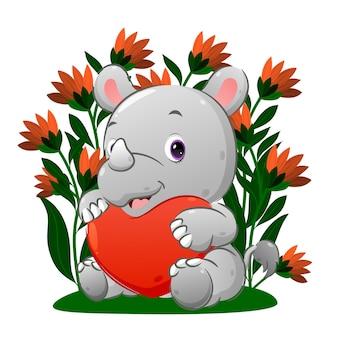 Детеныш носорога держит цветной воздушный шарик в форме сердца рукой, изображающей иллюстрацию