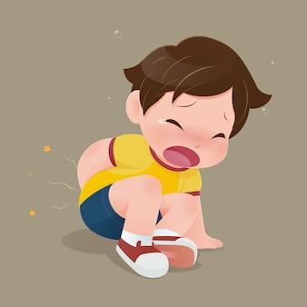 Мальчик в желтой рубашке страдает от боли в заднице