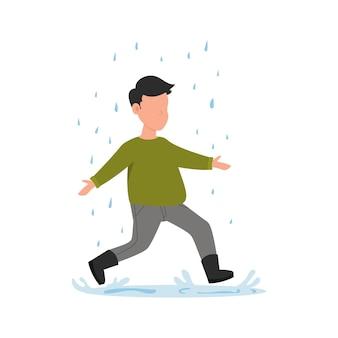 Мальчик бежит под дождем. осенние забавы. ребенок в резиновых сапогах прыгает в лужу.