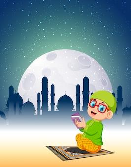 안경 소년은 밝은 달빛에 알 꾸란을 읽고 있습니다