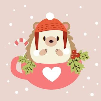 ヒイラギの葉とお菓子とピンクのカップに座っているかわいいハリネズミのキャラクター。かわいいハリネズミは、ピンクと白の雪の上に冬の帽子をかぶっています。