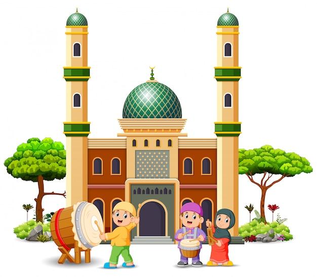 아이들은 모스크 앞에서 음악 도구를 가지고 놀고 있습니다