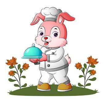멋진 토끼 요리사가 삽화의 움직일 수 있는 덮개 음식을 들고 있다