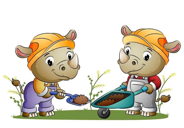 Пара-строитель носорог копает землю и движется к тачке иллюстрации