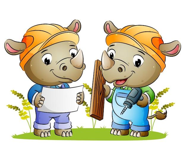 Пара-строитель носорог держит в руках доску с бумагой и деревянной иллюстрацией