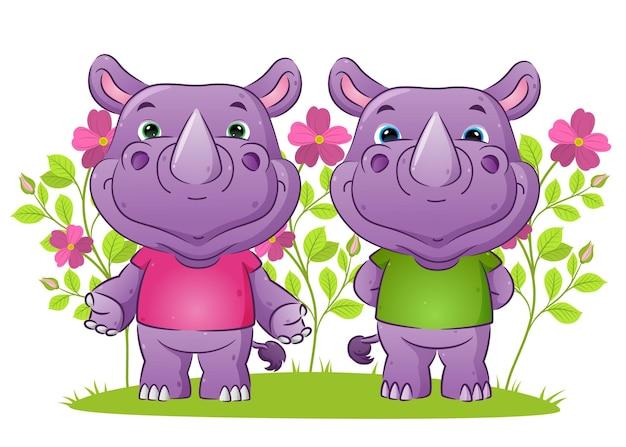 Пара дружелюбных носорогов в гостеприимной позе в саду, полном цветов.
