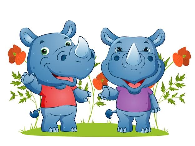 Пара счастливых носорогов машет рукой и дает иллюстрацию счастливой улыбки