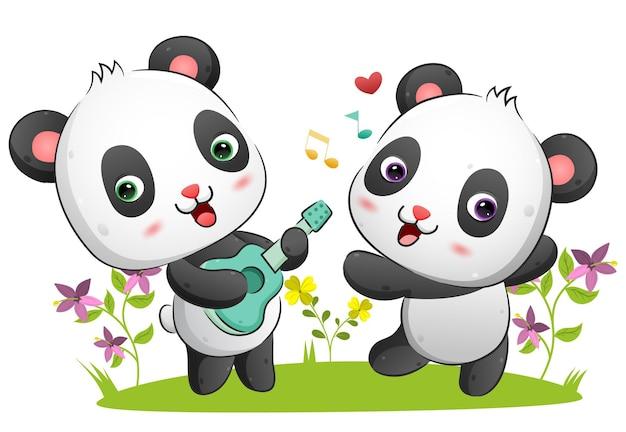 Пара панд играет на гитаре и танцует под музыку в парке.