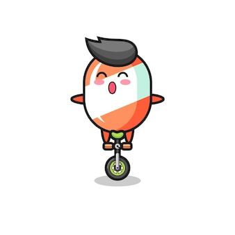귀여운 사탕 캐릭터가 서커스 자전거를 타고 있고, 티셔츠, 스티커, 로고 요소를 위한 귀여운 스타일 디자인