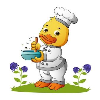 귀여운 오리 요리사는 삽화의 그릇에 숟가락을 끈다
