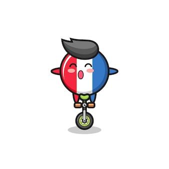 귀여운 프랑스 국기 배지 캐릭터가 서커스 자전거를 타고 있고, 티셔츠, 스티커, 로고 요소를 위한 귀여운 스타일 디자인