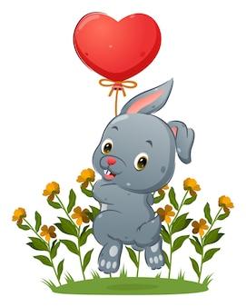 Милый кролик держит воздушный шар и прыгает в саду, полном цветов иллюстраций.