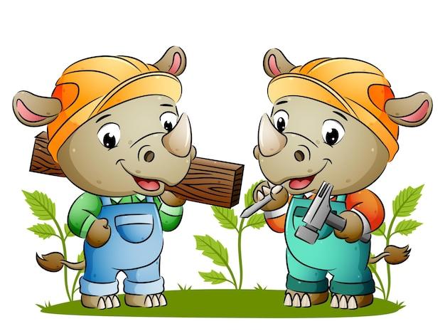 Два симпатичных носорога-строителя держат в руках строительные инструменты и деревянную доску с иллюстрациями