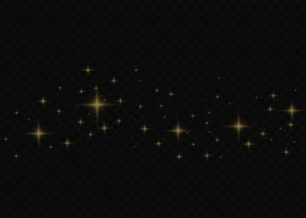 ほこりは黄色です。黄色い火花と金色の星が特別な光で輝いています。透明な背景にきらめきます。クリスマスライト効果。きらめく魔法のほこりの粒子。