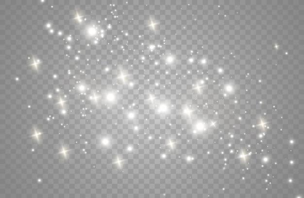 ほこりの火花と金色の星が特別な光で輝いています。透明な背景にきらめきます。クリスマスライト効果。きらめく魔法のほこりの粒子。