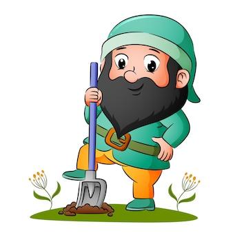 Карлик толкает лопату ногами, чтобы копать землю.