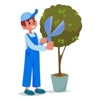 Садовник в рабочей форме и чепчике подрезает ножницами зеленый куст.