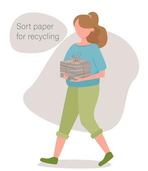 소녀는 분류 및 재활용을 위해 종이를 나 릅니다.