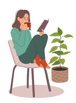 緑のパジャマを着た女の子がコーヒーを飲み、キッチンで読書