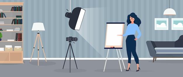 소녀는 카메라 앞에서 프레젠테이션을 하고 있습니다. 교사는 온라인으로 수업을 진행합니다. 블로그, 온라인 교육 및 회의의 개념. 삼각대에 카메라, 소프트박스.