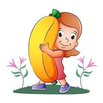 Девушка держит и показывает большой яркий банан иллюстрации