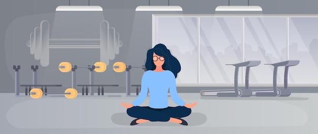 그 소녀는 체육관에서 명상을 하고 있다. 소녀는 체육관에서 요가를 합니다.