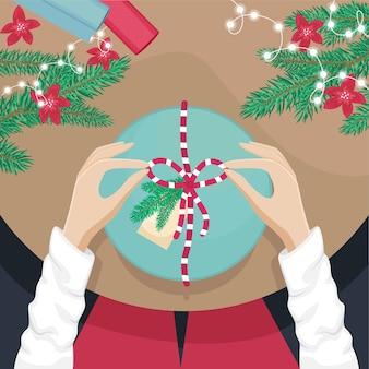 Девушка сидит за столом и открывает рождественский подарок
