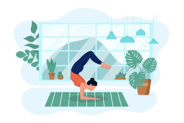 소녀는 집의 깔개에 거실에서 요가를 연습합니다. 운동하고 이완한다