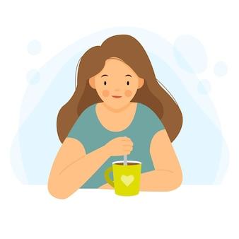 여자는 테이블에 앉아 여자는 차 또는 커피를 마시고 집에서 책상에 여자
