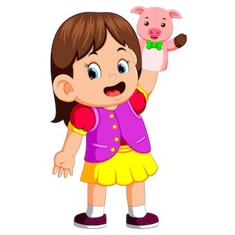 여자 아이는 귀여운 돼지 인형을 사용하고있었습니다