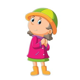 긴 스웨터를 입은 소녀가 밝은 삽화 모자를 사용하고 있습니다