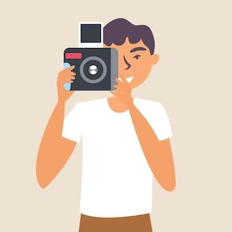 男はインスタントショットのためにカメラで写真を撮ります