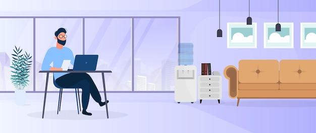 男はスタイリッシュなオフィスでラップトップで働いています。勉強、コンピューター、ソファ、ワードローブ、本のある本棚、壁の絵。在宅勤務。 。