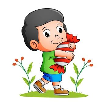 Счастливый мальчик держит большую конфету и гуляет по саду иллюстраций