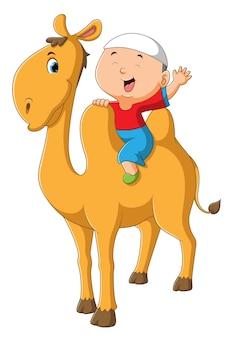 어린 소년은 귀여운 낙타 위에 앉아있다