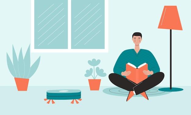 남자는 바닥에 앉아 책을 읽고 있습니다. 로봇 청소기가 근처에서 일하고 있습니다.