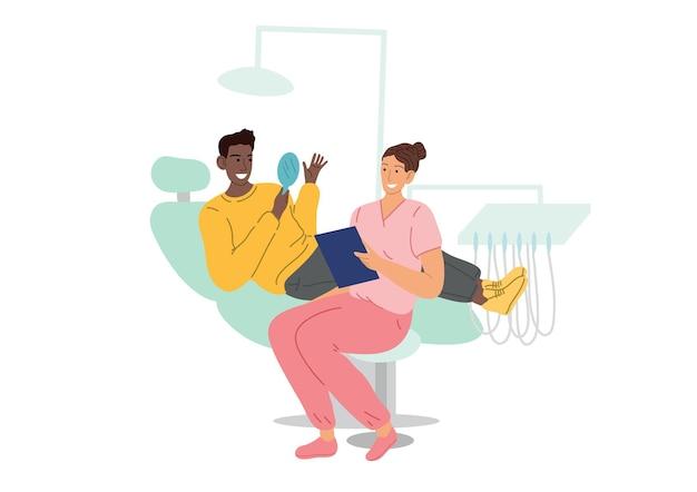 환자는 치과 의자에 앉아 거울을 들여다 보며 그의 치아와 하얀 미소를 봅니다. 치과 의사 약속에서.