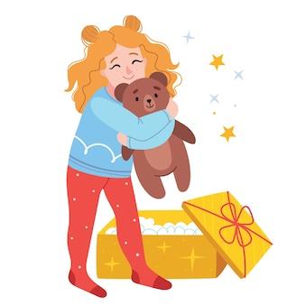 빨간 머리 소녀는 선물로 곰 인형을 받았습니다. 아이가 웃는다.