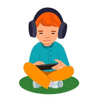 Redhaired 소년은 헤드폰을 착용하고 그의 손에 태블릿을 들고