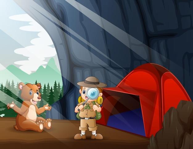 洞窟の中のサファリの少年とヒグマ